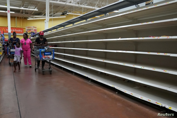 People walk past empty shelves where bread is normally sold in a Walmart store in advance of Hurricane Irma's expected arrival in North Miami Beach, Florida, Sept. 7, 2017.