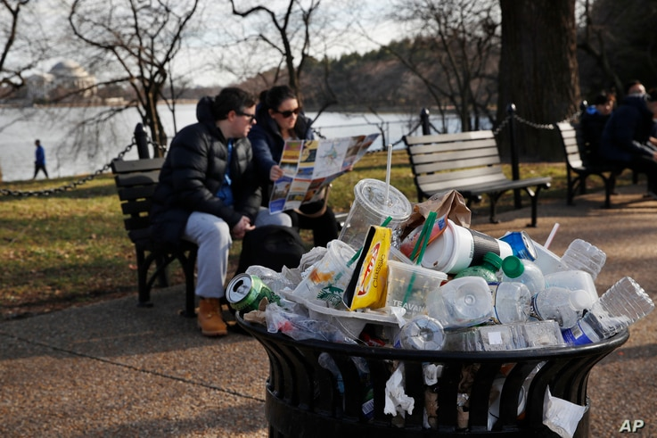 A trash can overflows as people site outside of the Martin Luther King Jr. Memorial by the Tidal Basin, Dec. 27, 2018, in Washington, during a partial government shutdown.