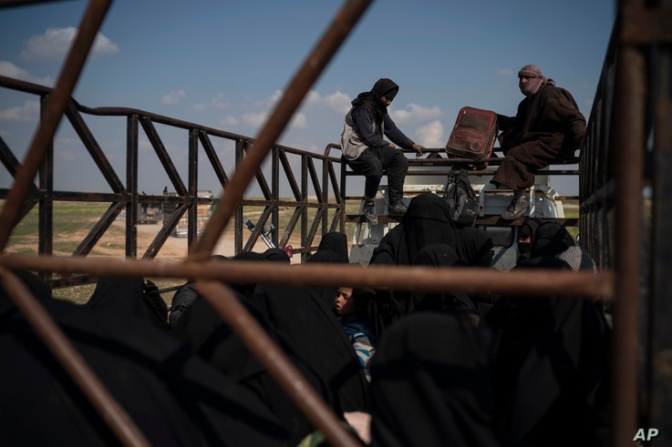 Men, women and children ride in the back of a truck in a convoy evacuating hundreds out of the last territory held by Islamic State militants in Baghuz, eastern Syria, Feb. 22, 2019. Small trucks carrying disheveled men, women and children left the I...