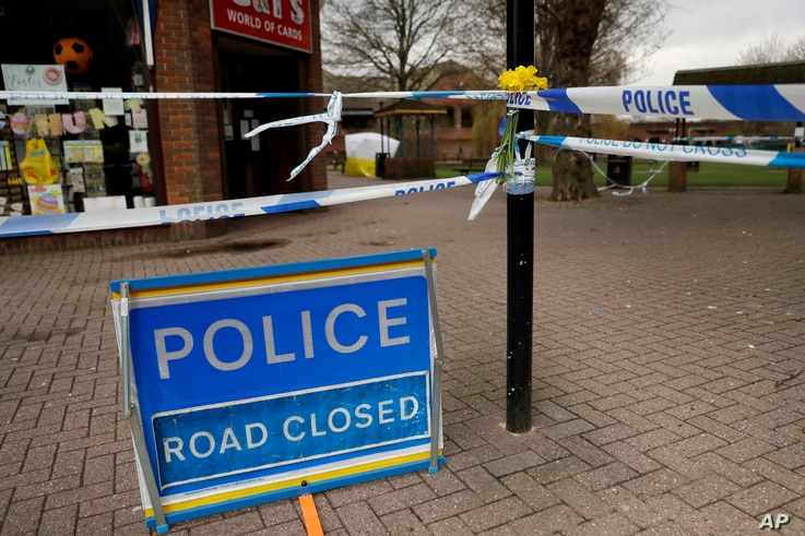 Daffodils are placed by a police cordon backdropped by a tent covering the area where former Russian double agent Sergei Skripal and his daughter were found critically ill, March 13, 2018.
