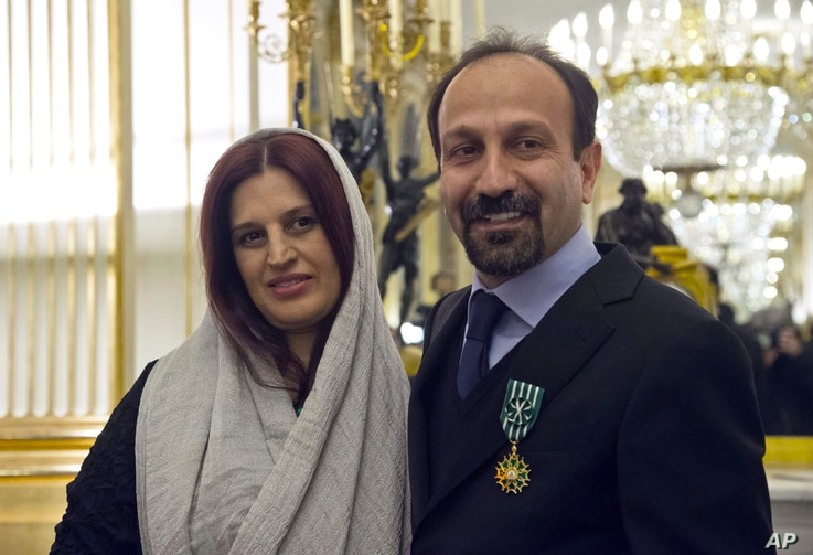 FILE - Iranian film director Asghar Farhadi and his wife, Parisa, pose after he was awarded the Officer of the Order of Arts and Letters medal, at the French Ministry of Culture, in Paris, France, Feb. 27, 2014.