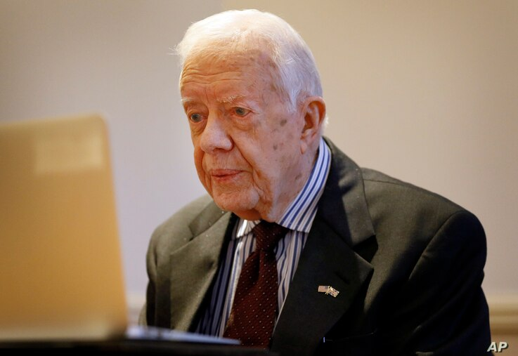 Former US President  Jimmy Carter listens during a video interview with the Associated Press via a laptop at a hotel in London, Tuesday, Feb. 2, 2016.