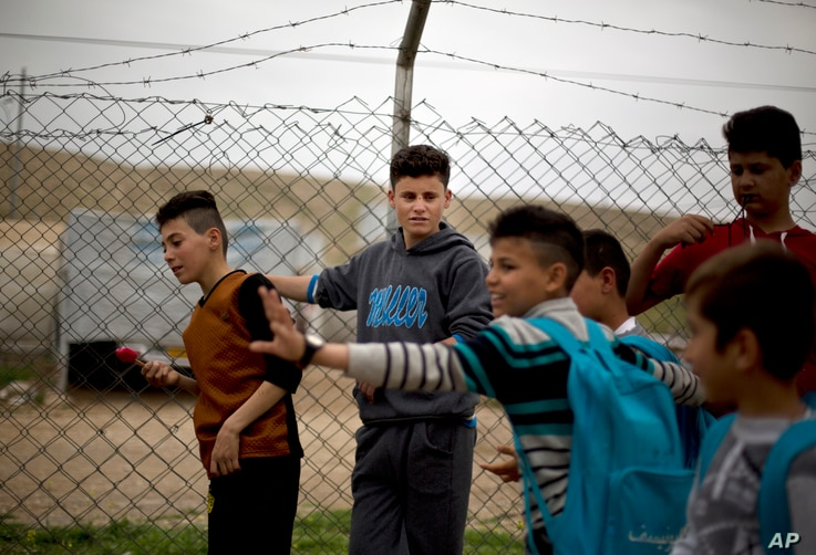FILE - Ahmed Ameen Koro, 17, center, talks with other children after school in the Esyan Camp for internally displaced people in Dahuk, Iraq, April 13, 2017. Ahmed was among 200 Yazidi boys captured by Islamic State militants and sent to a two-month ...