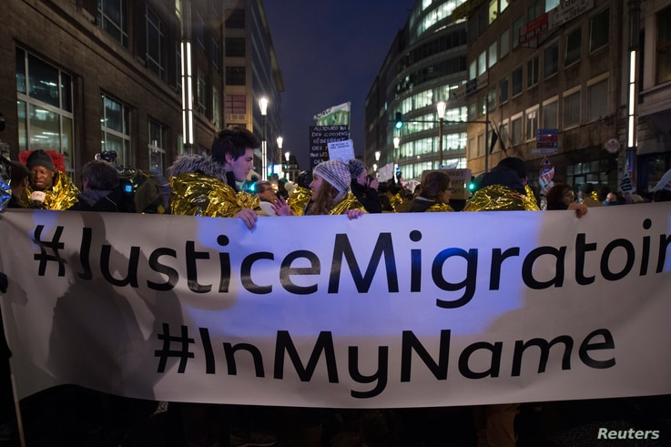 People take part in a protest in support of a new EU migration policy, a day before an EU leaders' meeting, in Brussels, Dec. 13, 2017.