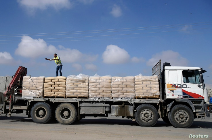 FILE - A Palestinian worker stands atop a truck loaded with bags of cement after entering Gaza, at the Kerem Shalom crossing in Rafah in the southern Gaza Strip, Nov.  10, 2014.