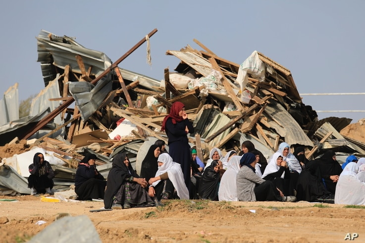 Bedouin women sit outside a demolished structure in the southern village of Umm al-Hiran, Wednesday, Jan. 18, 2017.