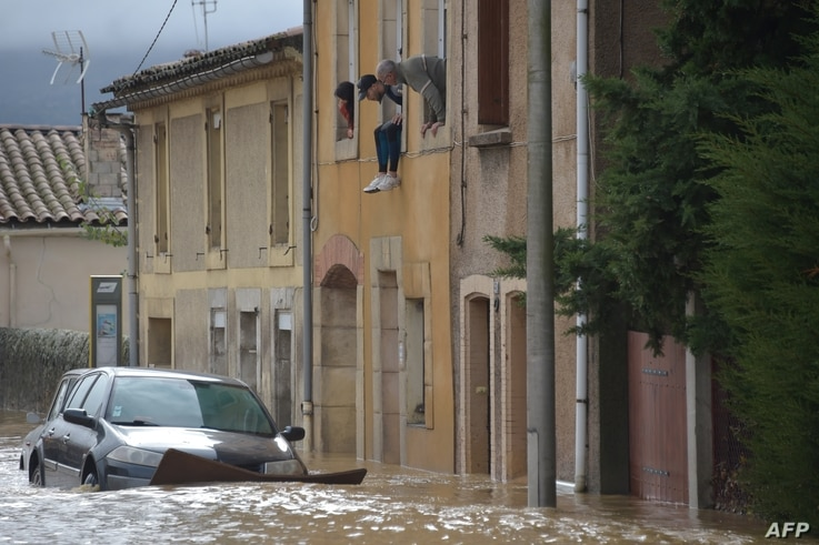 Residents look from their window above cars standing in a flooded street following heavy rains that saw rivers bursting banks on Oct. 15, 2018 in Trebes, near Carcassone, southern France.