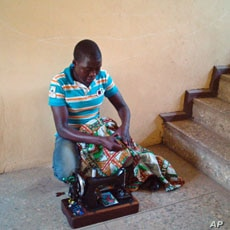 'Mobile tailor' Abubakar Mohammed sews outside a home, as he travels door-to-door with his sewing machine on his shoulder looking for work, in the capital, Abuja, Nigeria, February 15, 2012.