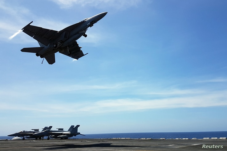An F18 fighter takes off from the deck of the USS Theodore Roosevelt while transiting the South China Sea, April 10, 2018.