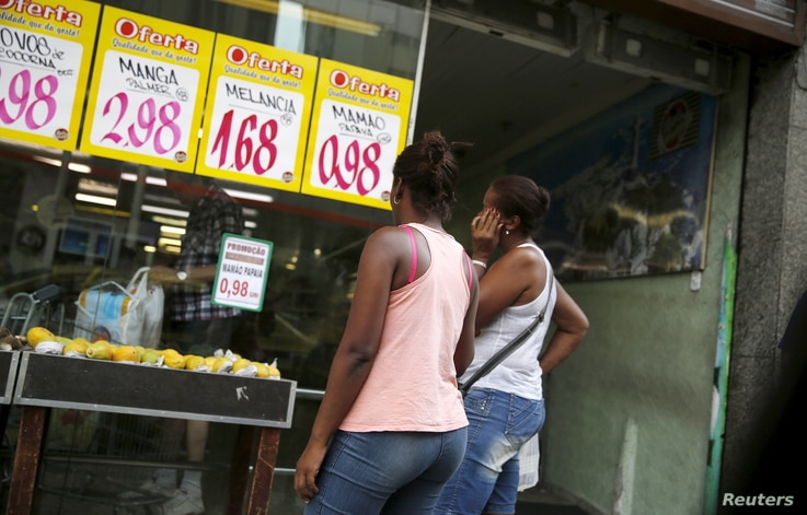 Women look at prices at a food market in Rio de Janeiro, Brazil, Jan. 21, 2016.