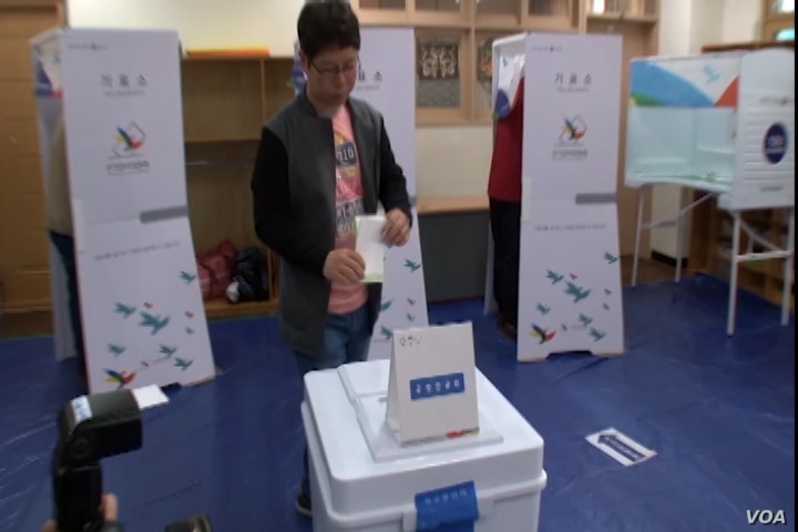 A South Korean male approaches the ballot box and casts his vote in Tuesday's election.