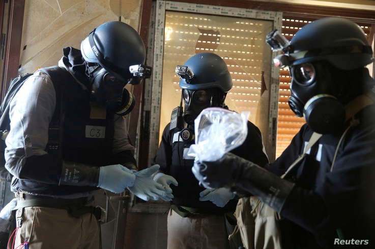 A U.N. chemical weapons expert, wearing a gas mask, holds a plastic bag containing samples from one of the sites of an alleged chemical weapons attack in the Ain Tarma neighbourhood of Damascus, Syria  Aug. 29, 2013.
