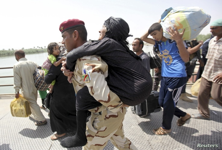 A member of Iraqi security forces carries an elderly woman across a bridge on the outskirts of Baghdad, May 24, 2015. Iraqi forces recaptured territory from advancing Islamic State militants near the recently-fallen city of Ramadi on Sunday, while in...