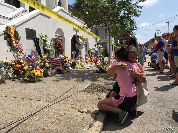 Mourners comfort each other in front of the Emanuel African Methodist Episcopal Church in Charleston, S.C., two days after a shooting left nine dead.