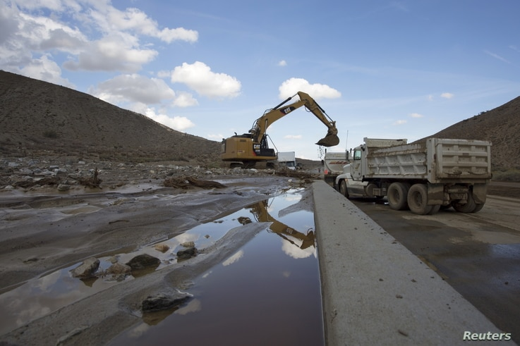 Workers dig out cars and trucks mired in mud and debris on State Route 58 near Tehachapi, California, about 97 kilometers (67 miles) outside of Los Angeles, Oct. 17, 2015.