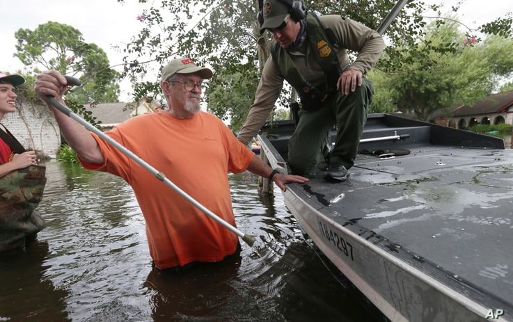 John Paul Klotz, 80, center, pulls a can out of floodwaters as U.S. Border Patrol Agent Steven Blackburn stands by to help Klotz board a boat during a search-and-rescue operation in a neighborhood inundated by Tropical Storm Harvey in Houston, Texas,...