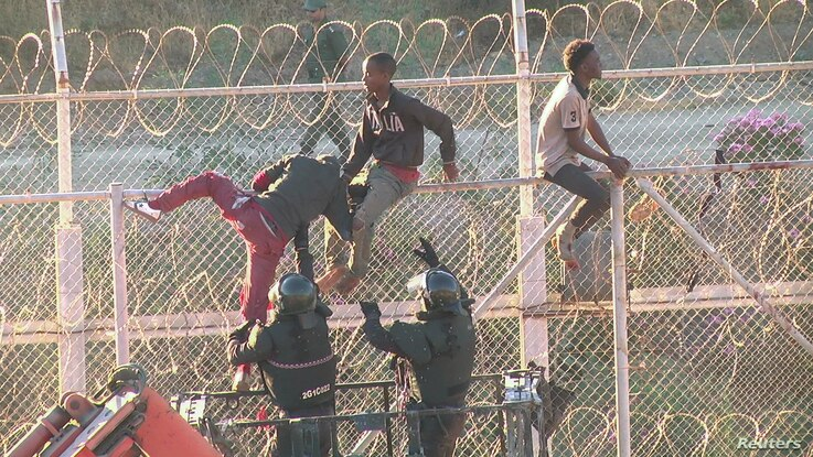 FILE - African migrants in this still image from video climb the border from Morocco to Spain's North African enclave of Ceuta, Spain, July 26, 2018.
