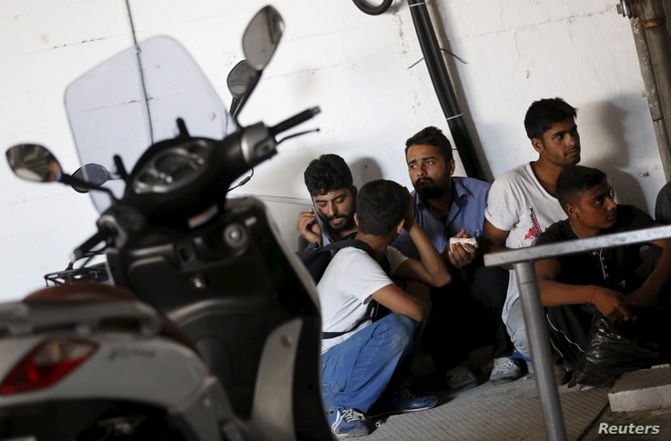 FILE - Migrants from Pakistan and Bangladesh wait after being detained by Turkish authorities at a bus terminal in the resort town of Bodrum, Turkey, Sept. 4, 2015.