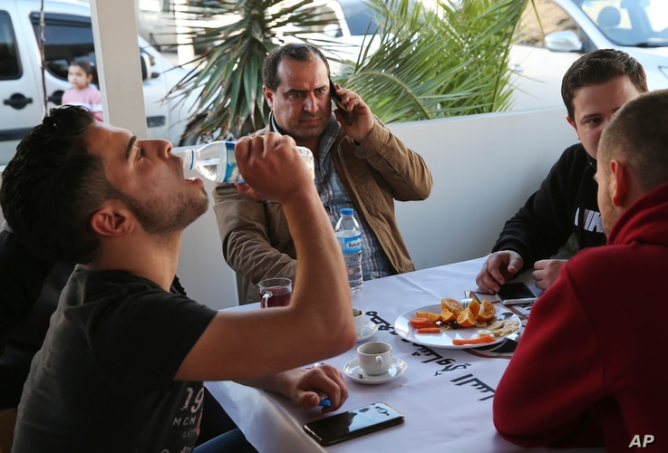 In this March 18, 2017, photo, Syrian Lt. Col. Ahmed al-Saoud, center, commander of the U.S.-backed Division 13 uses his mobile phone in a Syrian restaurant surrounded by aides and bodyguards, in Iskenderun, southern Turkey.