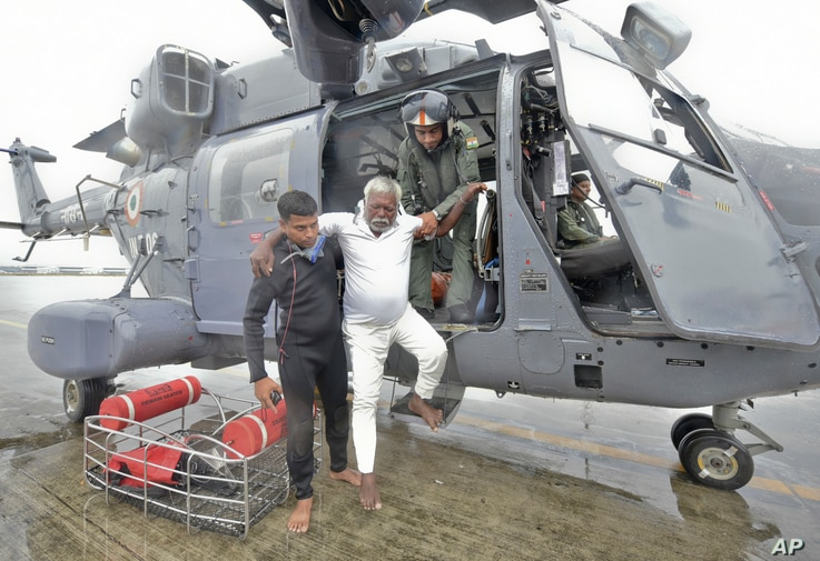 An Indian fisherman who was stranded in the Arabian Sea is escorted down from an Indian navy helicopter after being rescued in Thiruvananthapuram, Kerala state, India, Dec.1, 2017. Dozens of fishermen were rescued from the sea, which was very rough u...