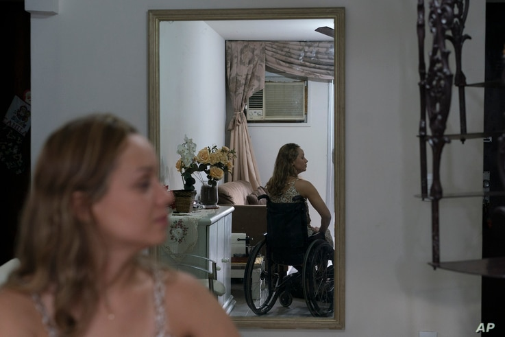 Camila Lima gives an interview from her wheelchair inside her home in Rio de Janeiro, Brazil, Jan. 18, 2019. Lima, who supports tighter gun laws, was hit by a stray bullet in the neck when she was 12 in her Rio neighborhood that left her paralyzed.