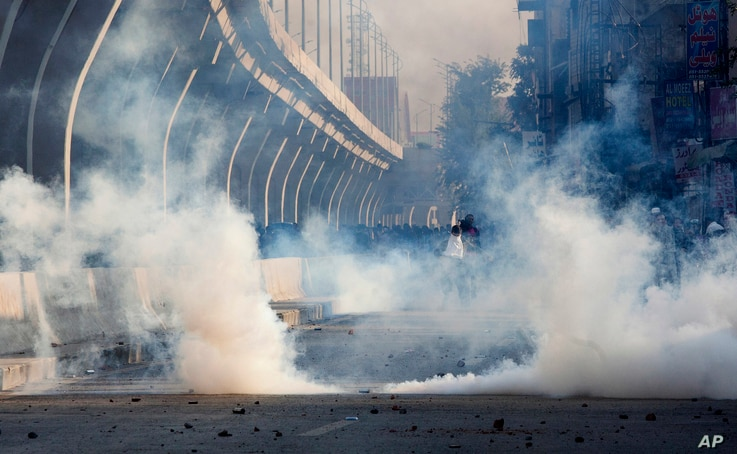 Police fire tear gas to disperse crowd protesting against the government in Rawalpindi, Pakistan, Friday, Oct. 28, 2016.