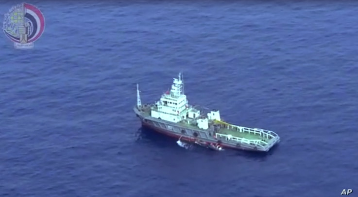 This still image taken from video posted Saturday, May 21, 2016, on the official Facebook page of the Egyptian Armed Forces spokesman shows an Egyptian ship collecting wreckage of EgyptAir flight 804.