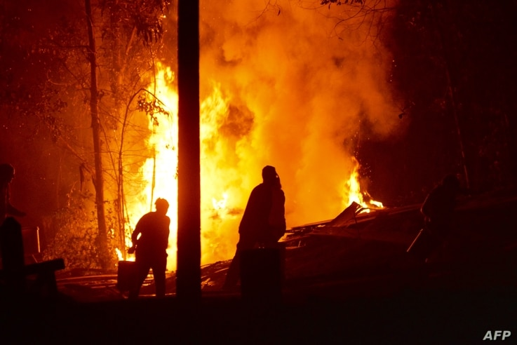 People work to put out a forest fire in Hualqui, 30 kilometres south of Concepcion, Biobio region, Chile, Jan. 27, 2017.