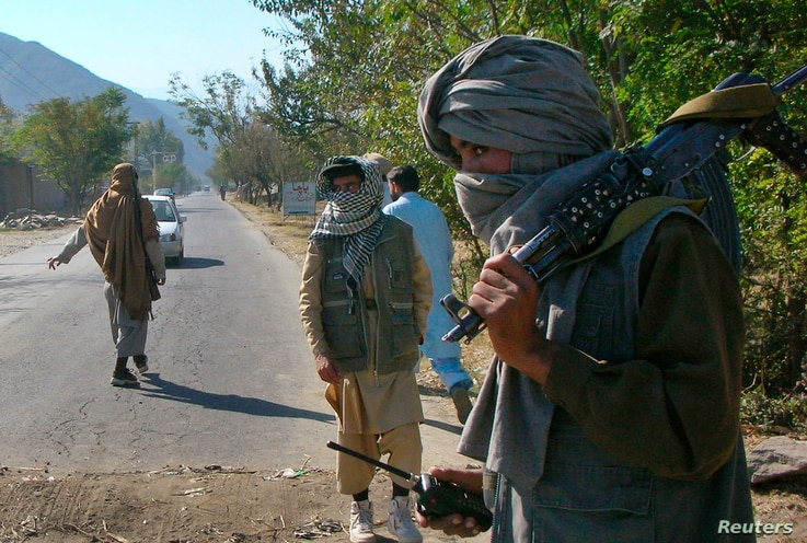 FILE - Masked Pakistani pro-Taliban militants who are supporters of Maulana Fazlullah, a hardline cleric, stand at a check post in Charbagh, a Taliban stronghold, near Mingora, the main town of Pakistan's Swat valley, Nov. 2, 2007.