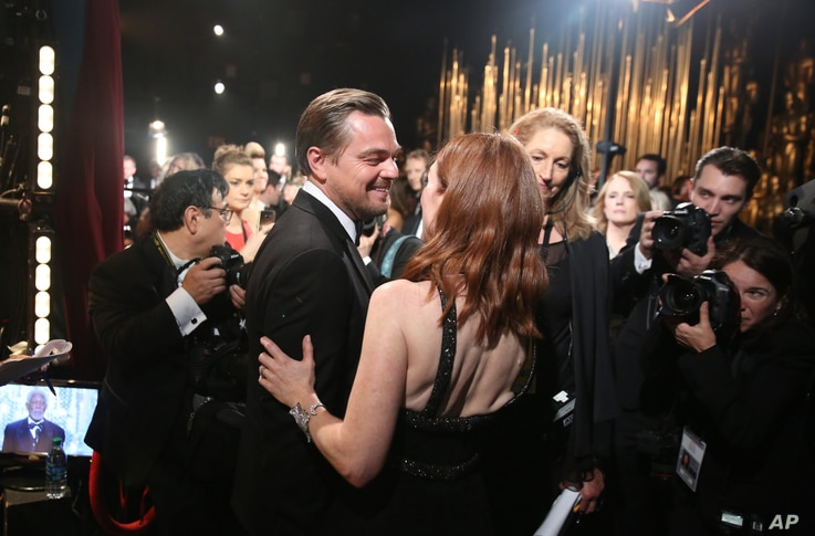 """Leonardo DiCaprio, winner of the award for best actor in a leading role for """"The Revenant"""", left, and Julianne Moore appear backstage at the Oscars, Feb. 28, 2016, at the Dolby Theatre in Los Angeles."""