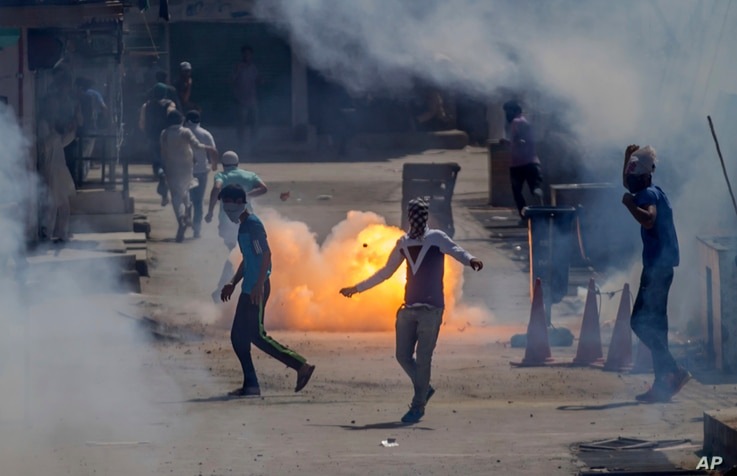 A tear gas shell fired by an Indian policeman explodes behind Kashmiri protesters during a protest in Srinagar, Indian controlled Kashmir, June 16, 2017.