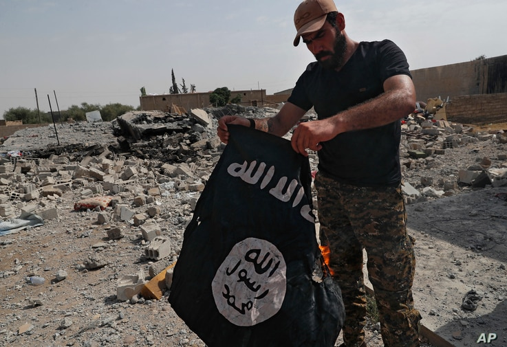 A fighter of the Christian Syriac militia that battles Islamic State militants under the banner of the U.S.-backed Syrian Democratic Forces burns an IS flag on the front line on the western side of Raqqa, northeast Syria, July 17, 2017.