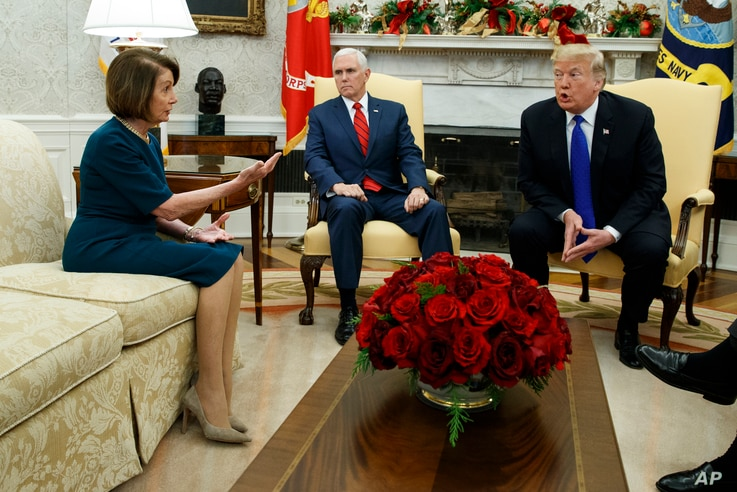 Vice President Mike Pence, center, looks on as House Minority Leader Rep. Nancy Pelosi, D-Calif., and President Donald Trump argue during a meeting in the Oval Office of the White House, Dec. 11, 2018, in Washington.