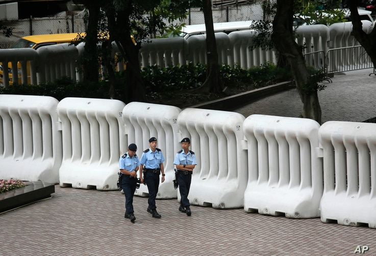 Police officers patrol in front of crowd-control barriers near the hotel where Zhang Dejiang, chairman of China's National People's Congress, will stay during his three-day visit to Hong Kong, May 17, 2016. The semiautonomous city has been the scene ...