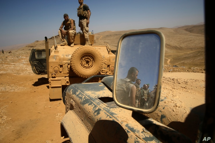 Lebanese soldiers rest on top of an armored personnel carrier during a media trip organized by the Lebanese army, on the outskirts of Ras Baalbek, northeast Lebanon Aug. 28, 2017. The Islamic State group has been expelled from its redoubt in the Qala...