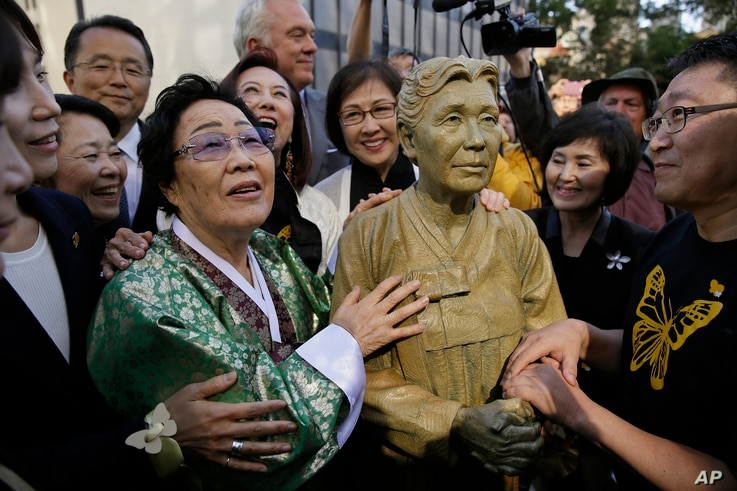 """Former World War II """"comfort woman"""" Yongsoo Lee, 89, of South Korea, stands by a statue of Haksoon Kim while looking at the """"Comfort Women"""" monument after it was unveiled, Sept. 22, 2017, in San Francisco."""