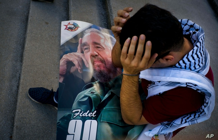 Palestinian medical student Adham Motawi, with an image of Fidel Castro, holds his head in disbelief during a gathering in Castro's honor in Havana, Cuba, the day after his death, Nov. 26, 2016.