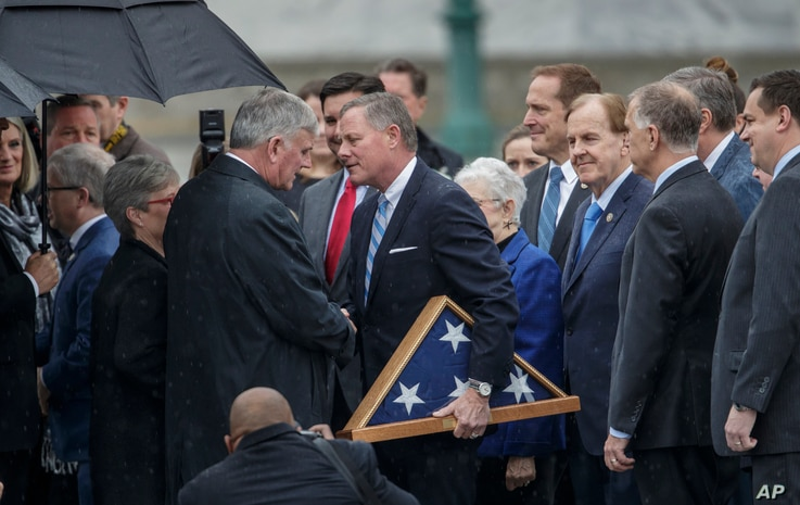 Sen. Richard Burr, R-N.C., holding the flag, reaches out to shake hands with Rev. Franklin Graham, the son of the late Rev. Billy Graham, on the East Front of the U.S. Capitol in Washington.