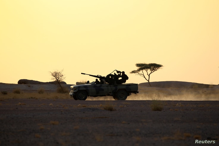 The Polisario Front soldiers drive a pick-up truck mounted with an anti-aircraft weapon during sunset in Bir Lahlou, Western Sahara, Sept. 9, 2016.