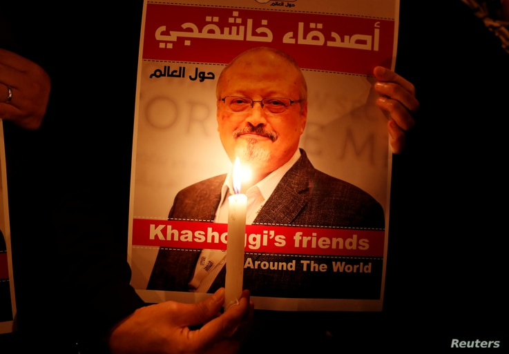 FILE - A protester holds a poster with a picture of slain Saudi journalist Jamal Khashoggi, outside Saudi Arabia's consulate in Istanbul, Turkey, Oct. 25, 2018.