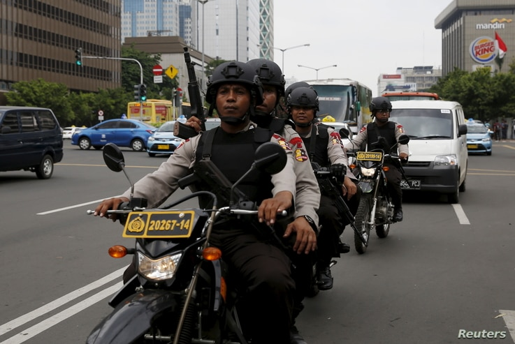 Indonesian policemen ride motorcycles as they patrol near the bomb blast site at Thamrin business district in Jakarta, Jan. 15, 2016.