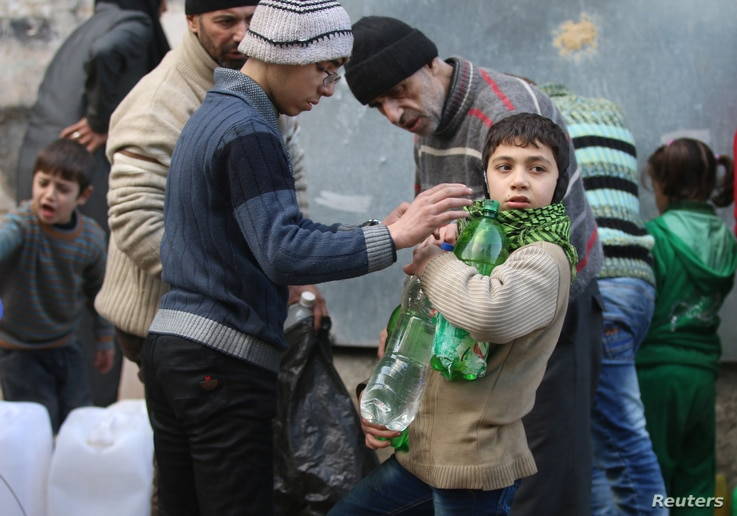 Civilians fill containers and bottles with water in a rebel-held besieged area of Aleppo, Syria, Dec. 10, 2016.