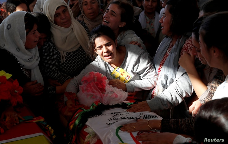 FILE - Mourners weep over the coffin of a Syrian journalist killed by the Islamic State militants on the frontline in Deir al-Zour, during a funeral in Kobani, Syria, Oct. 14, 2017.