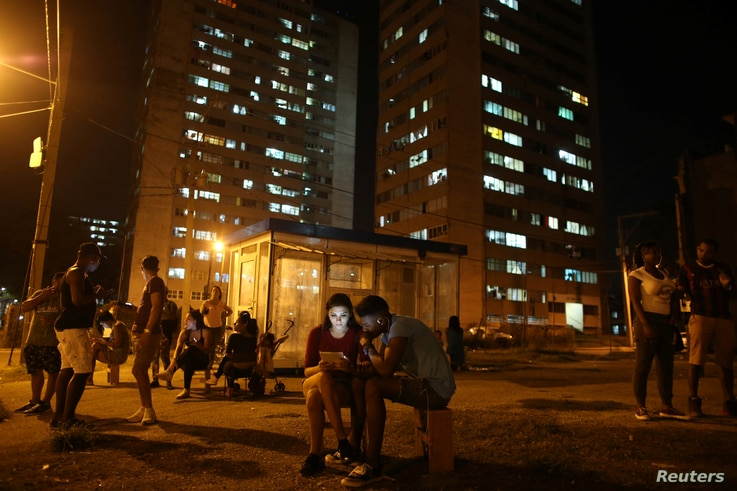 Carolina Gutierrez (center left), 17, and Neuil Valdez, 18, use mobile phones to connect to the internet at a hotspot in downtown Havana, Cuba, Dec. 12, 2016.