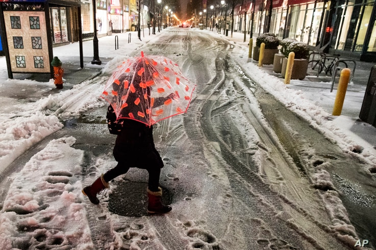 A woman crosses a street during a winter storm in Philadelphia, March 14, 2017.