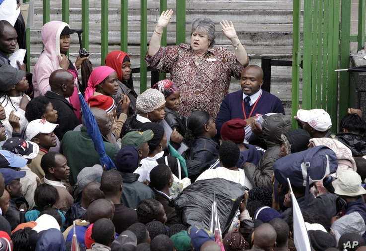 An immigration official addresses Zimbabweans outside an immigration office in downtown Johannesburg, South Africa, December 15, 2010, as they attempt to become legal.