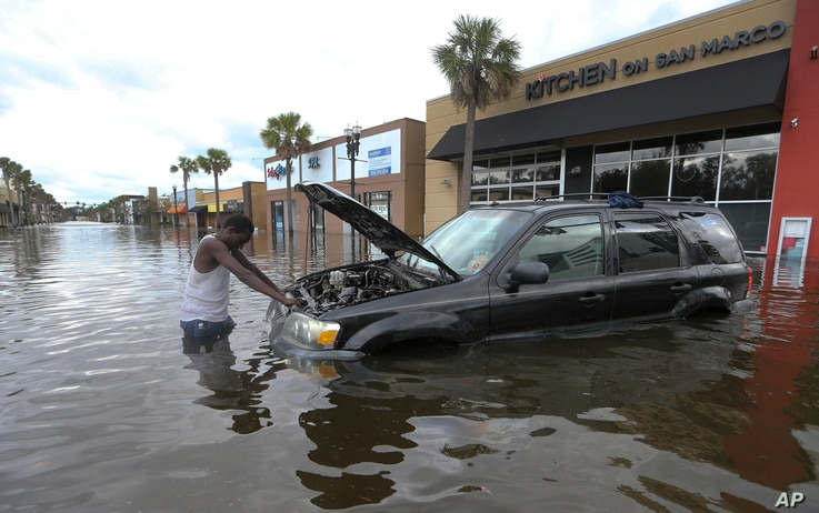 A man tries to figure out how to salvage his flooded vehicle in the wake Hurricane Irma, Sept. 11, 2017, in Jacksonville, Florida.
