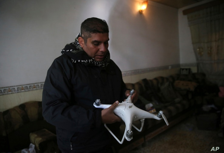 FILE - Iraqi special forces Lt. Col. Ali Hussein holds a destroyed drone used by Islamic State militants, which was shot down by his brigade, in the Bakr front line neighborhood, in Mosul, Iraq, Nov. 25, 2016.