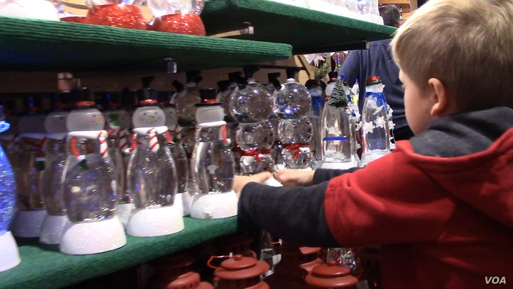 Snowman snow globes that light up are a favorite for one young shopper. (E.Celeste/VOA)