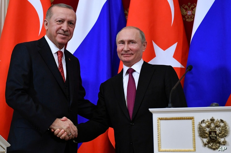 Russian President Vladimir Putin, right, shakes hands with Turkey's President Recep Tayyip Erdogan after their joint news conference following the talks in the Kremlin in Moscow, Russia, Jan. 23, 2019.